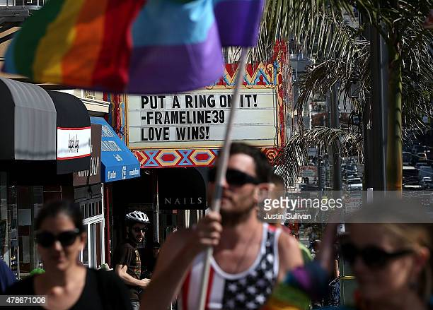A samesex marriage supporter holds a pride flag next to the marquee at the Castro Theatre that reads love wins while celebrating the US Supreme Court...