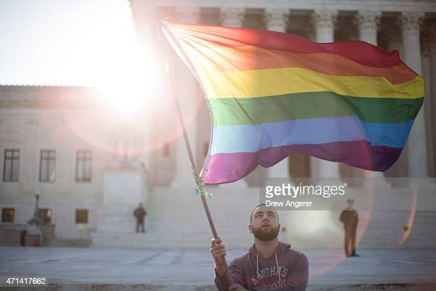 Samesex marriage supporter Vin Testa of Washington DC waves a rainbow pride flag near the Supreme Court April 28 2015 in Washington DC On Tuesday the...