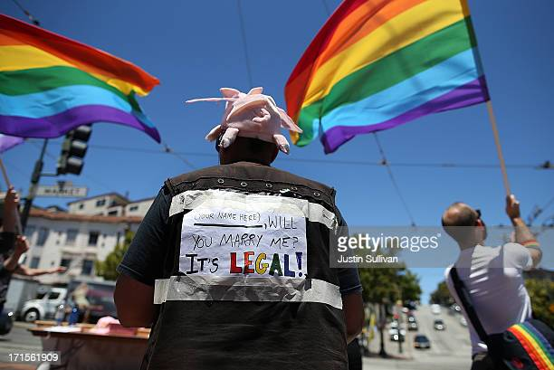 A samesex marriage supporter wears a sign on her back as she celebrates on the corner of Market and Castro on June 26 2013 in San Francisco...