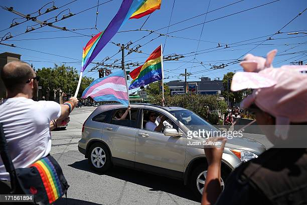 Samesex marriage supporters wave pride flags from a car as they drive by the corner of Market and Castro on June 26 2013 in San Francisco California...