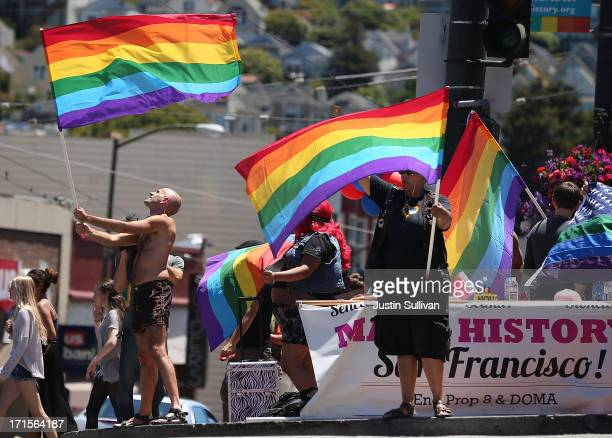 Samesex marriage supporters wave pride flags on the corner of Market and Castro on June 26 2013 in San Francisco California The Supreme Court of the...