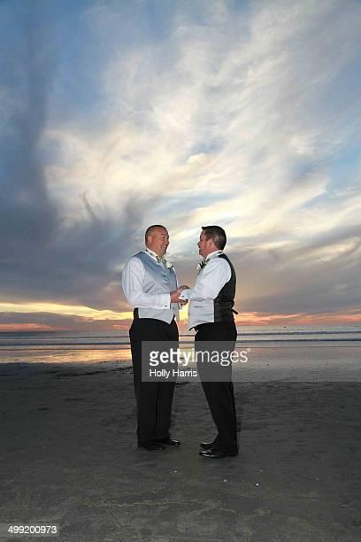 Same-sex wedding on beach at sunset