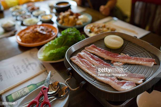 Samgyeopsal cooking on a butane grill waiting to be chopped up and served in lettuce wraps
