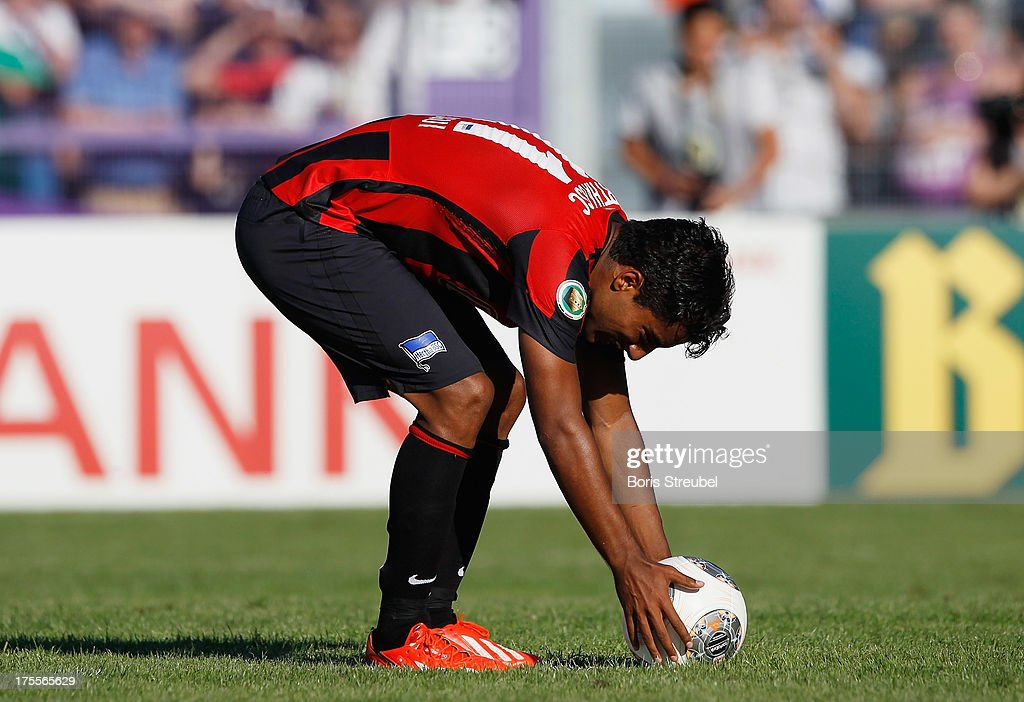Sami Allagui of Hertha BSC poses the ball to score his team's third goal by penalty during the DFB Cup first round match between VfR Neumuenster and Hertha BSC Berlin at Gruemmi-Arena on August 4, 2013 in Neumuenster, Germany.