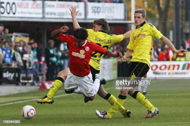 Sami Allagui of Mainz is challenged by Marcel Schmelzer and Sven Bender of Dortmund during the Bundesliga match between FSV Mainz 05 and Borussia...