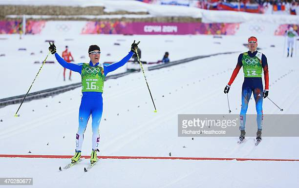 Sami Jauhojaervi of Finland celebrates as crosses the line to win the gold medal with team mate Iivo Niskanen of Finland ahead of Nikita Kriukov of...