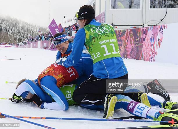Sami Jauhojaervi of Finland celebrates with team mate Iivo Niskanen of Finland and compatriots AinoKaisa Saarinen and Kerttu Niskanen of Finland...