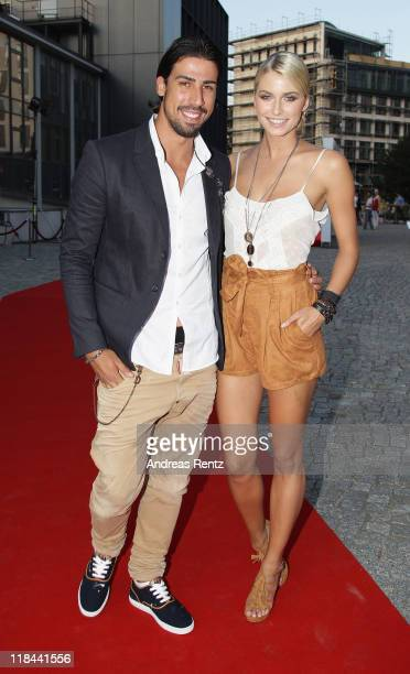 Sami Khedira and Lena Gercke attend the Guido Maria Kretschmer Show during MercedesBenz Fashion Week Berlin Spring/Summer 2012 at the KPM on July 7...