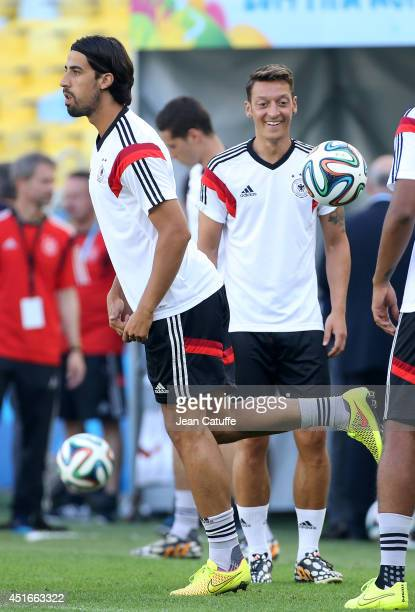 Sami Khedira and Mesut Ozil of Germany warm up during the practice session on the eve of the 2014 FIFA World Cup Brazil Quarter Final match between...