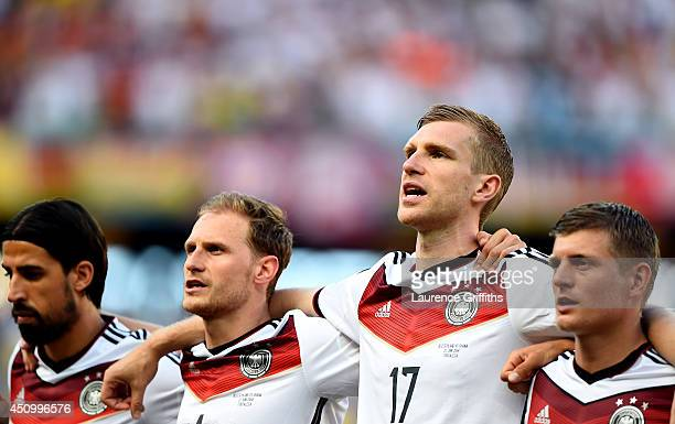 Sami Khedira Benedikt Hoewedes Per Mertesacker and Toni Kroos of Germany sing the National Anthem prior to the 2014 FIFA World Cup Brazil Group G...