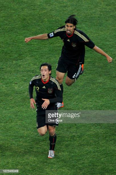 Sami Khedira follows Mesut Oezil of Germany as he celebrates scoring the opening goal as during the 2010 FIFA World Cup South Africa Group D match...