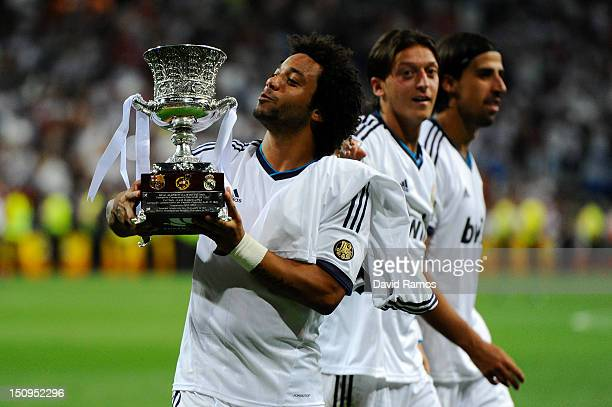 Sami Khedira Mesut Ozil and Marcelo Vieira of Real Madrid CF celebrates with the trophy after defeating FC Barcelona during the Super Cup second leg...