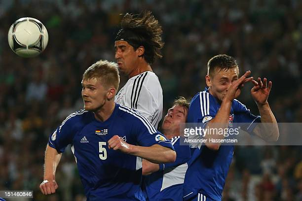 Sami Khedira of Germany battles for the ball with Odmar Faer of Faeroe Islands and his team mates Pol Johannus Justinusen and Hallur Hansson during...
