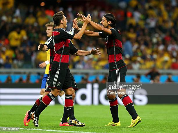 Sami Khedira of Germany celebrates scoring his team's fifth goal with his teammate Mesut Oezil during the 2014 FIFA World Cup Brazil Semi Final match...