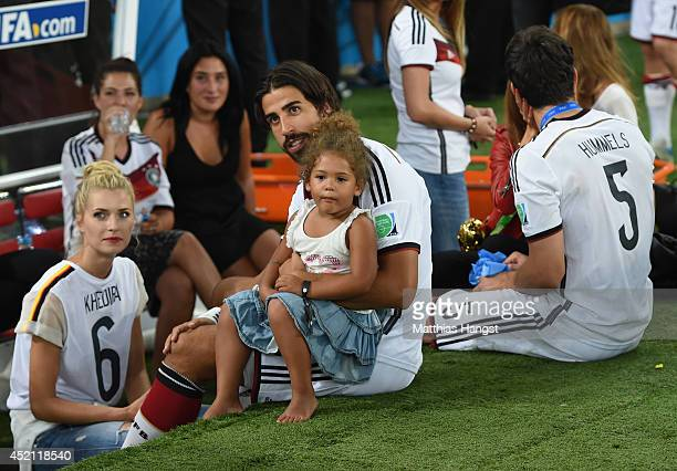 Sami Khedira of Germany celebrates with girlfriend Lena Gercke and Jerome Boateng daughter after defeating Argentina 10 in extra time during the 2014...