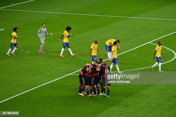 Sami Khedira of Germany celebrates with teammates scoring his team's fifth goal as Brazil players look dejected during the 2014 FIFA World Cup Brazil...