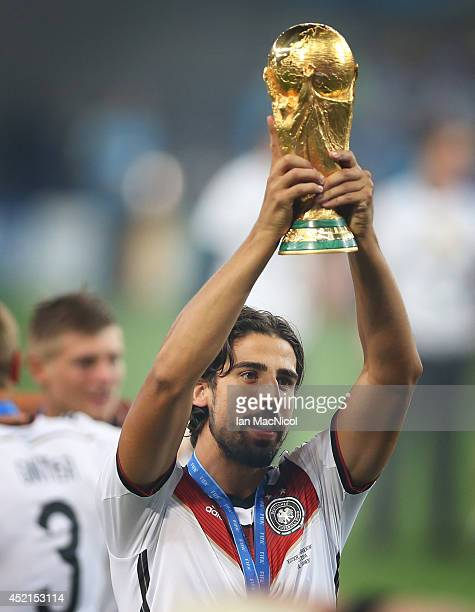 Sami Khedira of Germany holds the trophy a loft during the 2014 World Cup final match between Germany and Argentina at The Maracana Stadium on July...