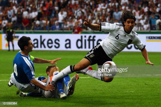 Sami Khedira of Germany is challenged by Emir Spahic and Adnan Mravac of Bosnia during the international friendly match between Germany and...