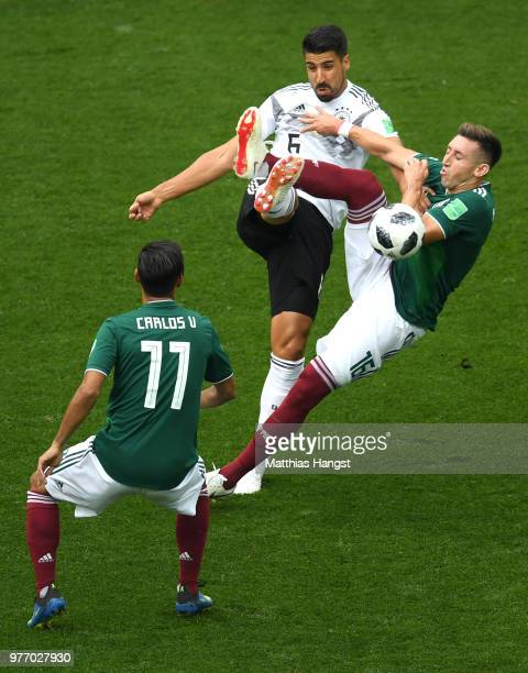 Sami Khedira of Germany is challenged by Hector Herrera and Carlos Vela of Mexico during the 2018 FIFA World Cup Russia group F match between Germany...