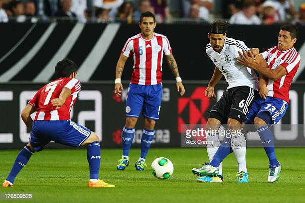 Sami Khedira of Germany is challenged by Richard Ortiz Victor Ayala and Jose Ariel Nunez of Paraguay during the international friendly match between...