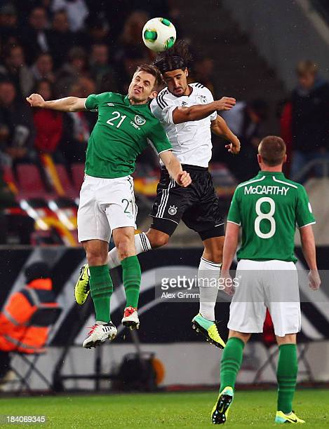 Sami Khedira of Germany jumps for a header with Kevin Doyle of Ireland during the FIFA 2014 World Cup Group C qualifiying match between Germany and...
