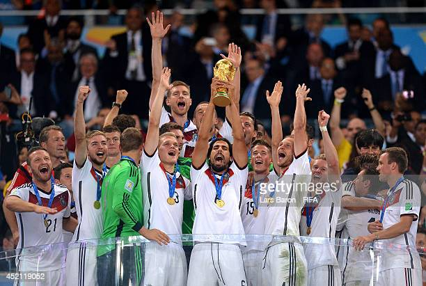 Sami Khedira of Germany lifts the World Cup trophy to celebrate with his teammates during the award ceremony after the 2014 FIFA World Cup Brazil...