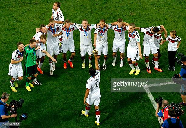 Sami Khedira of Germany raises the World Cup trophy to his teammates in celebration after defeating Argentina 10 in extra time during the 2014 FIFA...