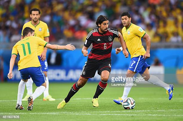 Sami Khedira of Germany runs past Oscar of Brazil with the ball during the 2014 FIFA World Cup Brazil Semi Final match between Brazil and Germany at...