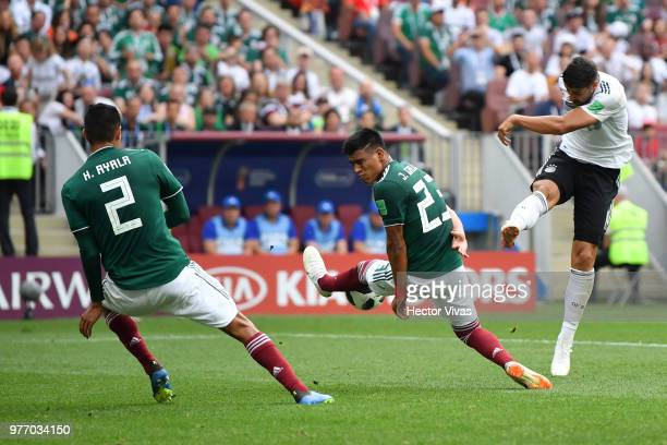 Sami Khedira of Germany shoots past Jesus Gallardo and Hugo Ayala of Mexico during the 2018 FIFA World Cup Russia group F match between Germany and...