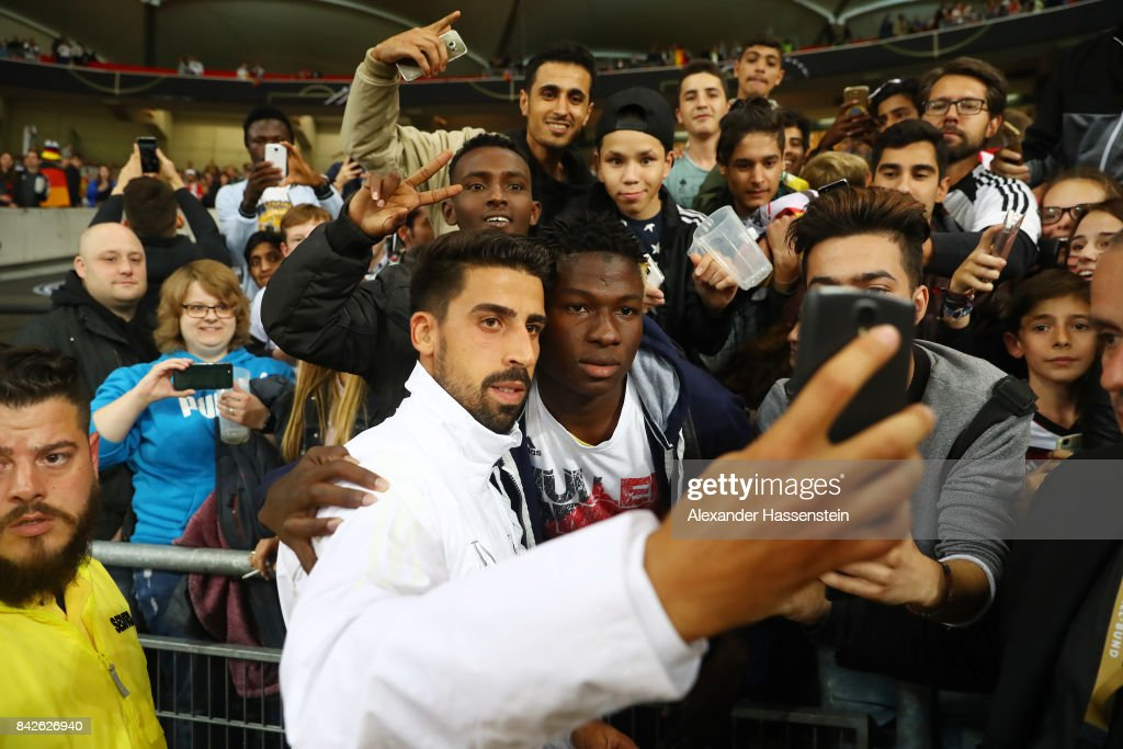 Sami Khedira of Germany takes selfies with fans after the FIFA 2018 World Cup Qualifier between Germany and Norway at Mercedes-Benz Arena on September 4, 2017 in Stuttgart, Baden-Wuerttemberg.
