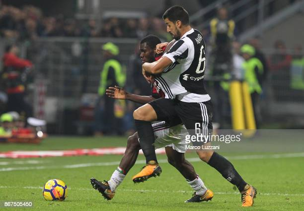 Sami Khedira of Juventus FC is pulled by his shirt by Franck Kessie of AC Milan during the Serie A match between AC Milan and Juventus at Stadio...
