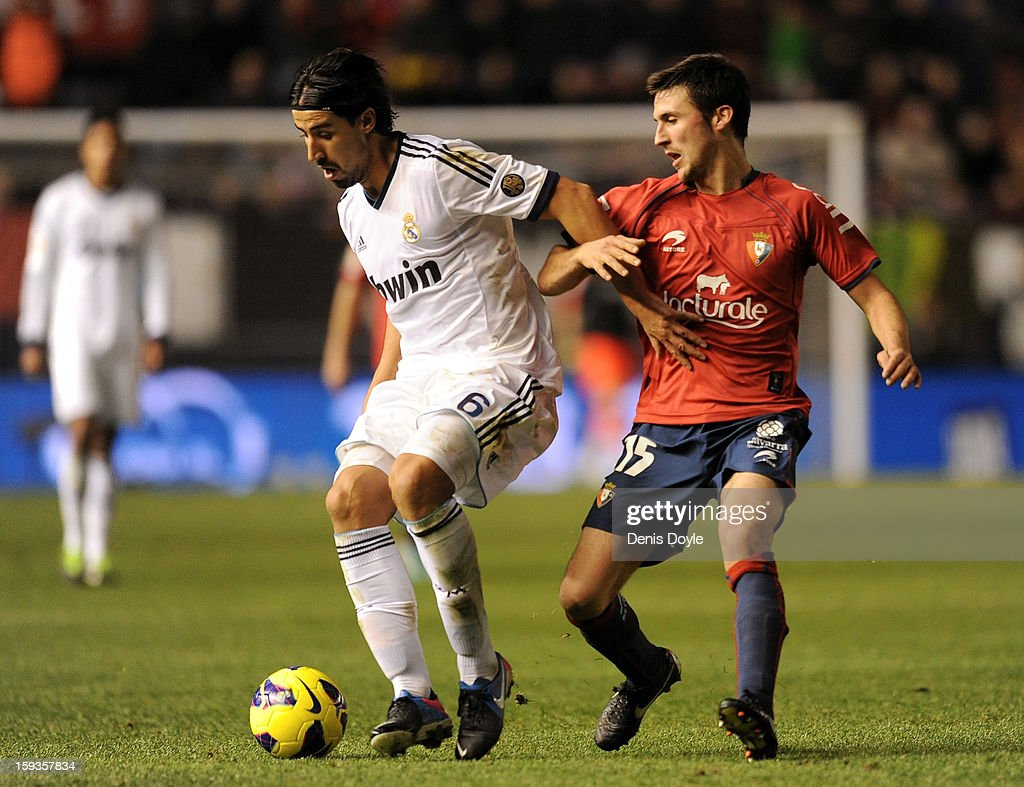 Sami Khedira (L) of Real Madrid battles for the ball against Oier Sanjurjo of Osasuna during the La Liga match between Osasuna and Real Madrid at estadio Reino de Navarra on January 12, 2013 in Pamplona, Spain.