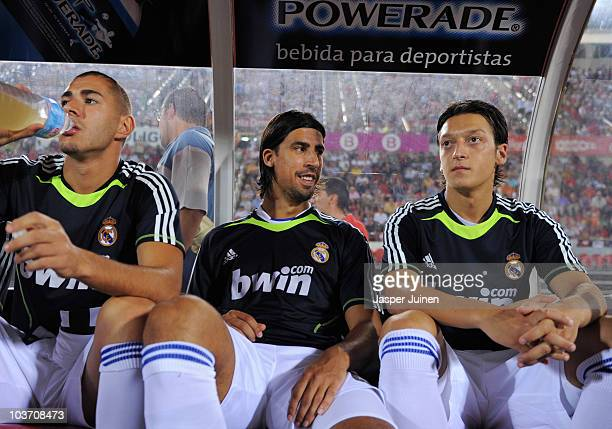 Sami Khedira of Real Madrid sits on the bench flanked by his teammates Mesut Ozil and Karim Benzema during the La Liga match between Mallorca and...