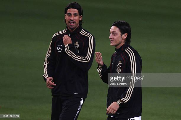 Sami Khedira walks past Mesut Oezil during a training session of the German national football team at the Astana Arena on October 11, 2010 in Astana,...