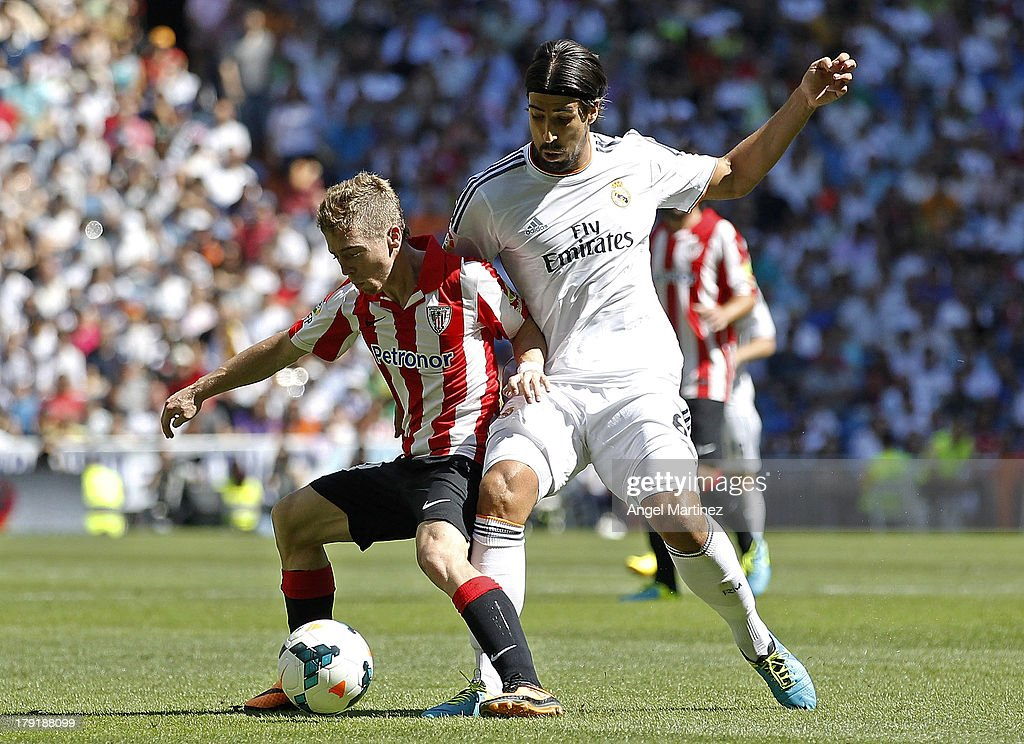 Sami Khedria of Real Madrid challenges Iker Muniain of Athletic Club during the La Liga match between Real Madrid and Athletic Club at Estadio Santiago Bernabeu on September 1, 2013 in Madrid, Spain.