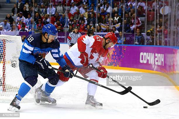 Sami Lepisto of Finland and Alexander Radulov of Russia fight for the puck during the Men's Ice Hockey Quarterfinal Playoff on Day 12 of the 2014...