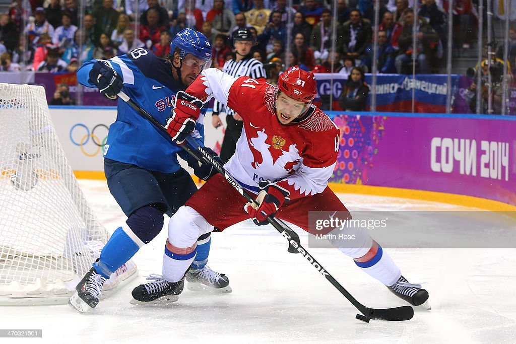 Sami Lepisto #18 of Finland challenges Nikolai Kulyomin #41 of Russia for the puck during the Men's Ice Hockey Quarterfinal Playoff on Day 12 of the 2014 Sochi Winter Olympics at Bolshoy Ice Dome on February 19, 2014 in Sochi, Russia.