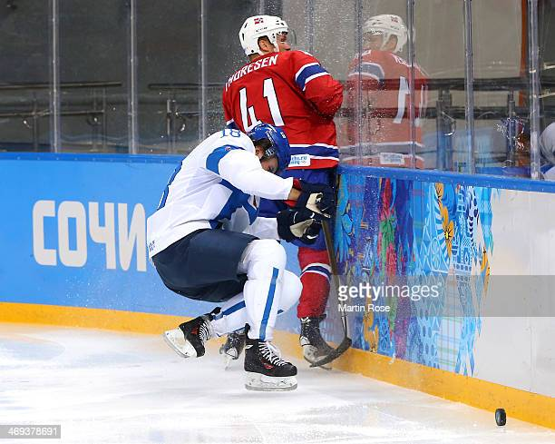 Sami Lepisto of Finland collides with Patrick Thoresen of Norway along the boards during the Men's Ice Hockey Preliminary Round Group B game on day...