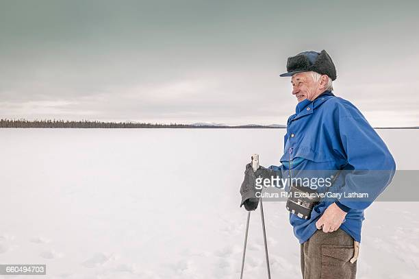 Sami reindeer herder on snow covered landscape looking away smiling, Lapland, Sweden