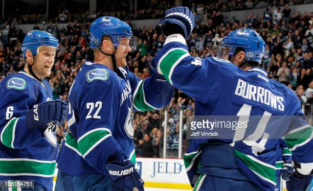 Sami Salo and Alex Burrows congratulate Daniel Sedin of the Vancouver Canucks after his third goal against the Colorado Avalanche during an NHL game...