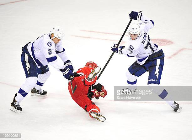 Sami Salo and Victor Hedman of the Tampa Bay Lightning send Chad LaRose of the Carolina Hurricanes crashing to the ice during play at PNC Arena on...