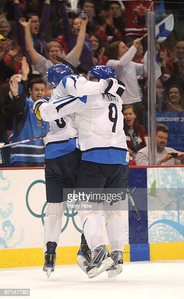 Sami Salo of Finland celebrates with Mikko Koivu after scoring a goal in the first period during the ice hockey men's bronze medal game between...