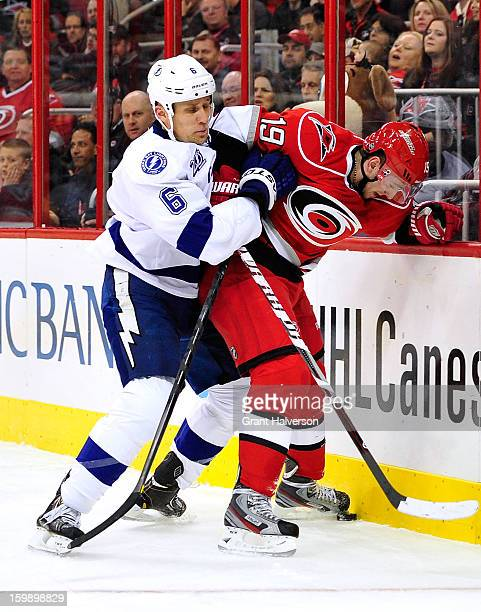 Sami Salo of the Tampa Bay Lightning checks Jiri Tlusty of the Carolina Hurricanes into the boards during play at PNC Arena on January 22 2013 in...
