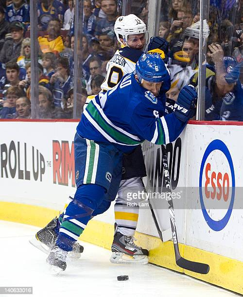 Sami Salo of the Vancouver Canucks hits Cody Hodgson of the Buffalo Sabres along the end boards during the first period in NHL action on March 03...