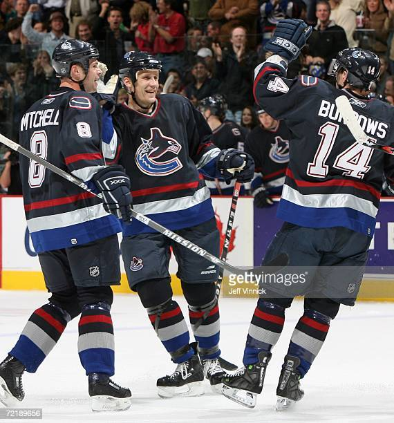 Sami Salo of the Vancouver Canucks is congratulated by teammates Willie Mitchell and Alexandre Burrows after scoring against the Edmonton Oilers...