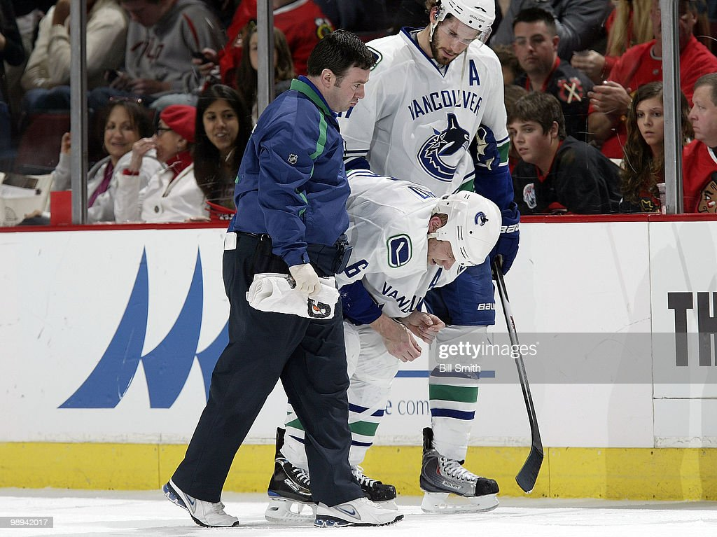 Sami Salo #6 of the Vancouver Canucks is helped off the ice by Head Athletic Trainer Mike Burnstein and teammate Ryan Kesler #17 after taking a shot to his midsection, at Game Five of the Western Conference Semifinals against the Chicago Blackhawks during the 2010 NHL Stanley Cup Playoffs on May 09, 2010 at the United Center in Chicago, Illinois.