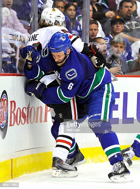 Sami Salo of the Vancouver Canucks pins Patrick Kane of the Chicago Blackhawks along the end boards during the second period in Game Four of the...