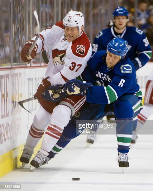 Sami Salo of the Vancouver Canucks tries to hold up Raffi Torres of the Phoenix Coyotes while chasing a loose puck during the first period in NHL...
