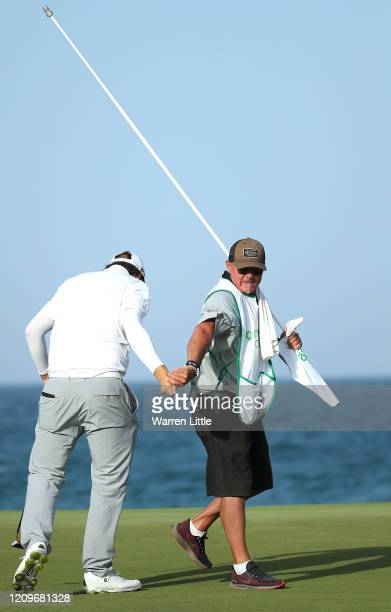 Sami Valimaki of Finland celebrates with caddie Kyle Roadley on the 18th green during the final round of the Oman Open at Al Mouj Golf Complex on...