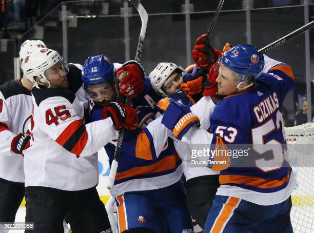 Sami Vatanen and Nico Hischier of the New Jersey Devils go up against Cal Clutterbuck and Casey Cizikas of the New York Islanders during the second...